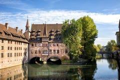 Nuremberg Heilig-Geist-Spital som reflekteras i vattnet av den Pegnitz floden Franconia Tyskland royaltyfri bild