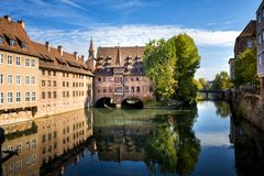 Free Nuremberg, Heilig-Geist-Spital Which Is Reflected In The Waters Of The Pegnitz River. Franconia, Germany Stock Photo - 130085200