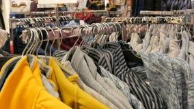 Nuremberg Niemcy, Grudzień, - 1, 2018: Ogromna liczba barwiący ciepli zima pulowery wiesza na wieszakach w sklepie zbiory wideo