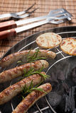 Nuremberg sausages or Bratwurst with potatoes and rosemary on grill Stock Photos