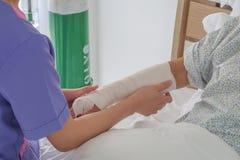 Nures applicerar resår förbinder till den brutna armen av den höga patienten arkivfoto