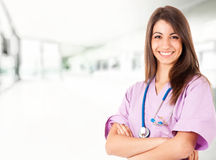 Nurse. Young nurse in an hospital hall while holding a stethoscope Stock Photos