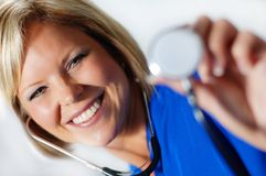 Nurse. Mature nurse in scrubs holding up stethoscope stock photo