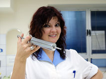 Nurse. Smiling while holding a really big injection Stock Images