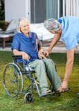 Nurse Adjusting Footrest For Senior Woman On Royalty Free Stock Photography