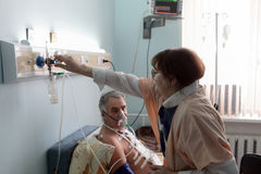 Nurse adjusting the level of oxygen. Nurse is adjusting the level of oxygen for a patient stock images