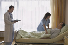 Nurse Adjusting Patient In Bed At Hospital Stock Photo