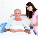 A nurse adjusting pillows for a senior patient. Caring nurse adjusting pillows for a senior patient in a hospital Royalty Free Stock Images