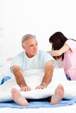 A nurse adjusting pillows for a senior patient. Female nurse adjusting pillows for a senior patient in a hospital Stock Photo