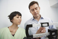 Nurse Adjusting Weighing Scale For Man. An Asian female nurse adjusting weighing scale for men at clinic royalty free stock photo