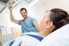 Nurse Adjusting Xray Machine For Patient. Male nurse smiling while adjusting xray machine for patient in examination room Royalty Free Stock Images