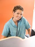 Nurse Answering Telephone While Working At. Portrait of happy nurse answering telephone while working at hospital reception Stock Photos