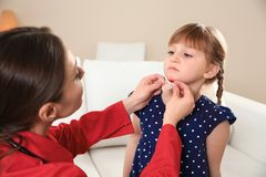 Nurse applying medical patch to little girl`s injured face indoors stock photos