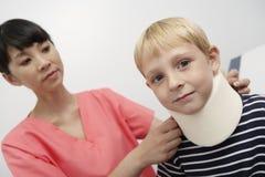Nurse applying neck brace Stock Image