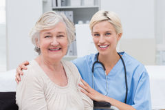 Nurse with arm around senior patient in clinic Royalty Free Stock Photography