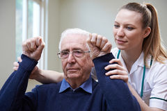 Nurse Assessing Stroke Victim By Raising Arms. Nurse Assesses Stroke Victim By Raising Arms stock photos