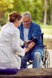 Nurse assessment of blood pressure elderly man in wheelchair Royalty Free Stock Photography