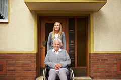 Nurse in assisted living project. Smiling elderly woman in front of a retirement home royalty free stock images