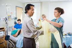Nurse Assisting Doctor In Wearing Operation Gown Royalty Free Stock Images