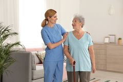 Nurse assisting elderly woman with cane royalty free stock image