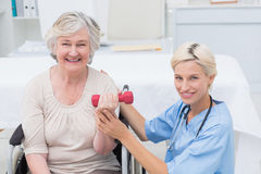 Nurse assisting female patient in lifting dumbbell Royalty Free Stock Photos