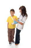 Nurse assisting an injured boy. Nurse or healthcare officer assisting with an arm sling on an injured boy Royalty Free Stock Photography
