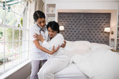 Nurse assisting patient on bed at home Stock Photography