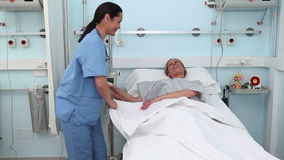 Nurse assisting a patient to lie down in a medical bed