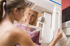 Nurse Assisting Patient Undergoing Mammogram stock photography