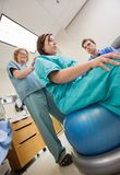 Nurse Assisting Pregnant Woman Sitting On Exercise Stock Photos