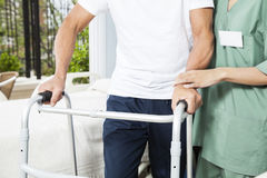 Nurse Assisting Senior Man With Walker In Rehab Center stock photo