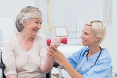 Nurse assisting senior patient in lifting dumbbell Royalty Free Stock Image