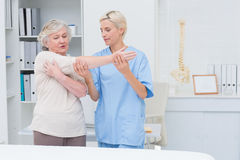 Nurse assisting senior patient in raising arm Stock Photo