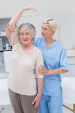 Nurse assisting senior patient in raising arm Stock Image