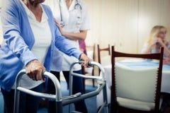 Nurse assisting a senior using a walker Stock Photos