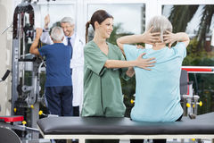 Nurse Assisting Senior Woman In Back Exercise In Rehab Center. Smiling female nurse assisting senior women in back exercise at rehab fitness center Royalty Free Stock Image