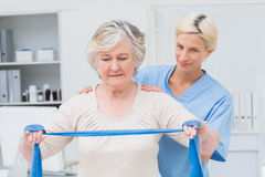 Nurse assisting senior woman in exercising with resistance band Stock Image