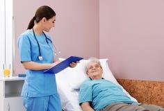 Nurse assisting senior woman lying on bed royalty free stock photos