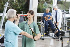 Nurse Assisting Senior Woman With Resistance Band Exercise Stock Images