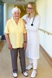 Nurse Assisting a Senior Woman Walking at Corridor royalty free stock photos