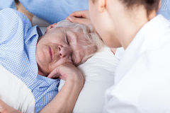 A nurse assists older woman Stock Photos