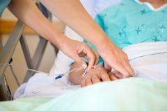 Nurse Attaching IV Drip On Male Patient's Hand Stock Image