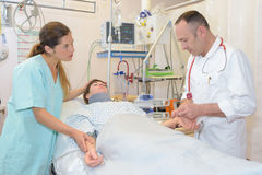 Nurse awaiting results doctor`s pulse test Stock Images