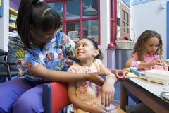 Nurse bandaging girls arm royalty free stock image