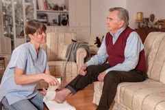 Nurse bandaging senior patient royalty free stock photo