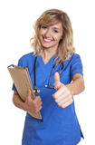 Nurse with blond hair and file showing thumb Stock Images