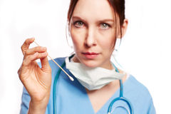 Nurse in blue Op clothing with stethoscope and cotton buds as Cu Stock Images
