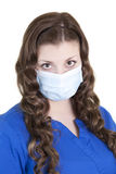 Nurse in Blue Scrubs with Mask. A young female health care worker with mask on covering her nose and mouth to prevent catching or spreading germs and disease Royalty Free Stock Photography