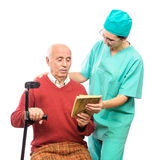 Nurse bringing books to old disabled person Royalty Free Stock Images