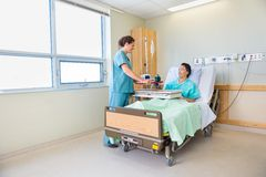 Nurse Bringing Breakfast For Male Patient In. Happy nurse bringing breakfast for mature male patient in hospital room Stock Image